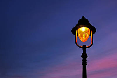 Dusk Poster featuring the photograph Lamppost Illuminated At Twilight by Mikel Martinez de Osaba