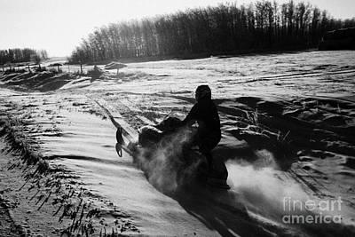 man on snowmobile crossing frozen fields in rural Forget canada Poster by Joe Fox