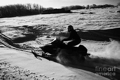 man on snowmobile crossing frozen fields in rural Forget Saskatchewan Poster by Joe Fox