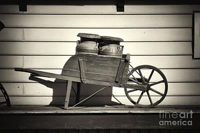Milk Jugs In A Wheelbarrow Poster by George Oze