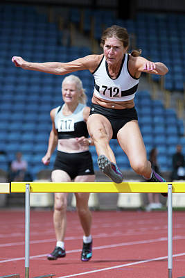 Senior Female Athlete Clears Hurdle Poster by Alex Rotas