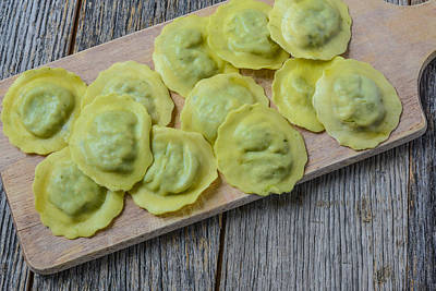 Spinach Ravioli On A Wood Cutting Board Poster by Brandon Bourdages
