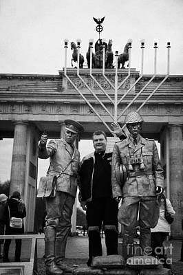 tourist posing for photograph with silver painted street entertainer dressed as east german guard Brandenburg gate Berlin Germany Poster by Joe Fox