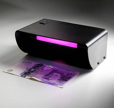 Ultraviolet Banknote Checker Poster by Science Photo Library