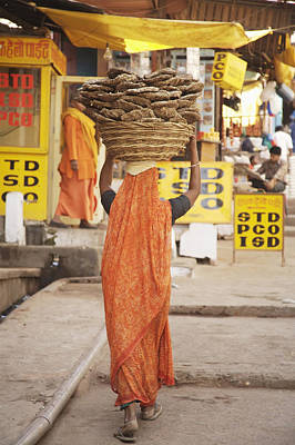 Woman Carrying Cow Dung In Basket On Poster by Paul Miles