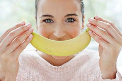Woman Holding A Banana In Front Of Face Poster by Ian Hooton