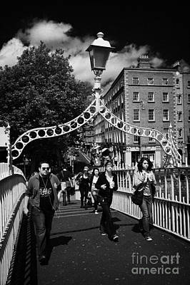 Pedestrians Crossing The Halfpenny Hapenny Bridge Over The River Liffey In The Centre Of Dublin City Poster by Joe Fox
