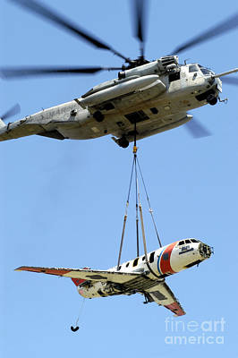 A Ch-53 Sea Stallion Lifts A Hu-25 Poster by Stocktrek Images