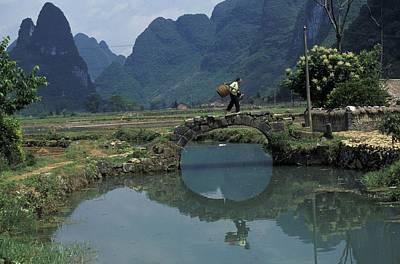 A Peasant Crosses A Stone Bridge Poster by Raymond Gehman
