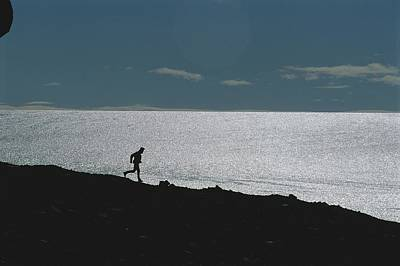 Silhouette Of Man Jogging Past A Bare Poster by Gordon Wiltsie