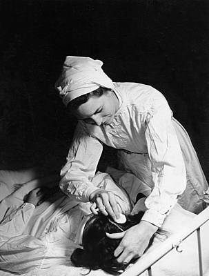 Nurse Tending To A Patient Poster by Underwood Archives