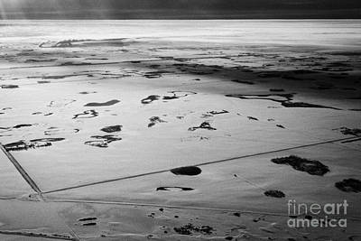Harsh Conditions Photograph - aerial view of snow covered prairies and remote isolated farmland in Saskatchewan Canada by Joe Fox