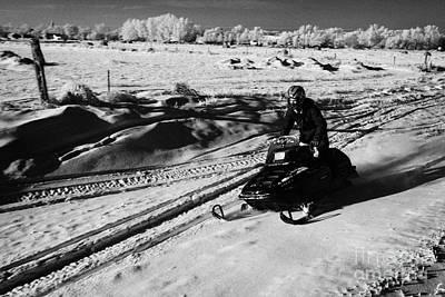 man on snowmobile crossing frozen fields in rural Forget Saskatchewan Canada Print by Joe Fox