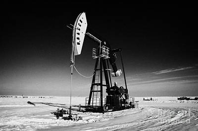 oil pumpjack in winter snow Forget Saskatchewan Canada Print by Joe Fox