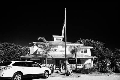 Raising Photograph - Raising The American Flag On A Flagpole Outside The Chamber Of Commerce Building In Key Largo Florid by Joe Fox