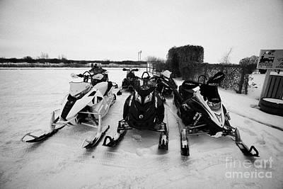Snowmobile Photograph - snowmobiles parked in Kamsack Saskatchewan Canada by Joe Fox