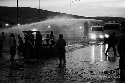Youths Rioting With Burned Out Car Being Hit By Water Canon On Crumlin Road At Ardoyne Print by Joe Fox