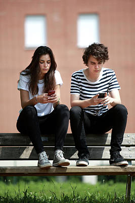 Teenage Couple Using Smart Phones Print by Mauro Fermariello