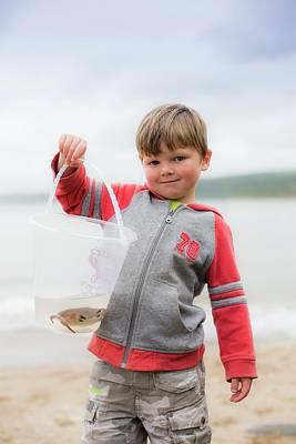 Candid Photograph - Boy Holding Crab by Samuel Ashfield