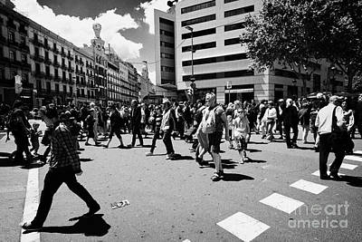 Crosswalk Photograph - People Walking Across Busy Pedestrian Crossing Placa De Catalunya Barcelona Catalonia Spain by Joe Fox