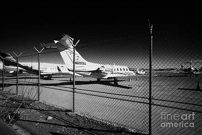 security chain link fencing with warning restricted area sign on the perimeter of mccarran airport L Print by Joe Fox