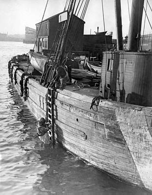 Wooden Ships Photograph - A Deep Sea Diver On A Boat by Underwood Archives