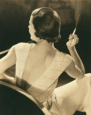Evening Gown Photograph - A Glamourous Woman Smoking by Underwood Archives