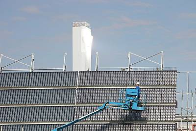A Man Cleans Solar Panels Print by Ashley Cooper