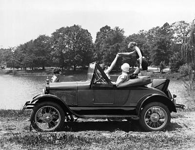 Helping Photograph - A Woman Exiting A Rumble Seat by Underwood Archives