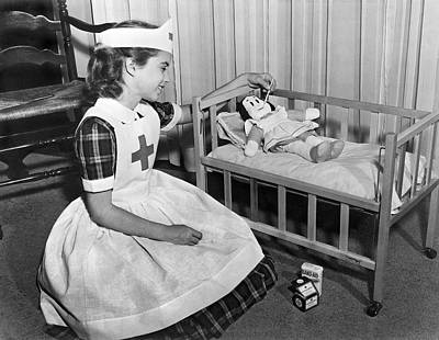 Recycling Photograph - A Young Girl Plays Nurse To Her Little Lulu Doll. by Underwood Archives