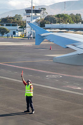 International Airport Photograph - Airport Worker Guides Jet Airliner by Jim West
