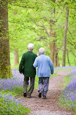 Pensioner Photograph - An Elderly Couple Walking by Ashley Cooper