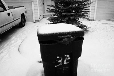 bag sticking out of litter waste bin covered in snow outside house in Saskatoon Saskatchewan Canada Print by Joe Fox