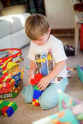 Boy Playing With Plastic Bricks Print by Samuel Ashfield