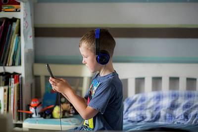 Boy Wearing Headphones Using Device Print by Samuel Ashfield
