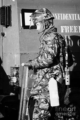 British Army Soldier In Riot Gear With Fire Extinguisher In Front Of Land Rover On Crumlin Road At A Print by Joe Fox