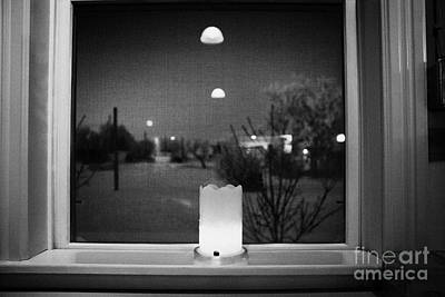 candle in the window looking out over snow covered scene in small rural village of Forget Saskatchew Print by Joe Fox