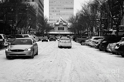 cars driving though snow covered streets in downtown Saskatoon Saskatchewan Canada Print by Joe Fox