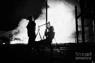 children play in playground at 11th night bonfire in Monkstown fire northern ireland Print by Joe Fox