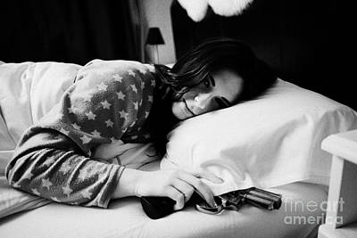 Early Twenties Woman Waking With Hand On Handgun Under Pillow At Night In Bed In A Bedroom Print by Joe Fox