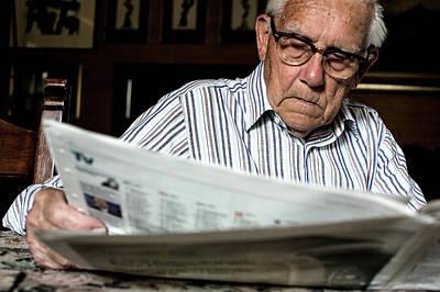 Elderly Man Reading A Newspaper Print by Mauro Fermariello