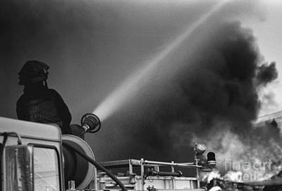Black And White Photograph - Fire Fighter Using Water Cannon by Tom Brickhouse