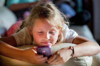 Adolescence Photograph - Girl Lying On Front Using A Smartphone by Samuel Ashfield