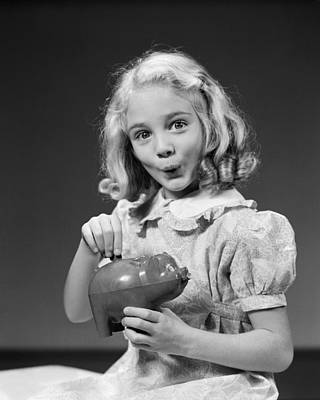Girl Putting Coin In Piggy Bank, C.1940s Print by H. Armstrong Roberts/ClassicStock