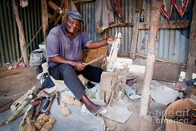 Carved Photograph - Kenya. December 10th. A Man Carving Figures In Wood. by Michal Bednarek