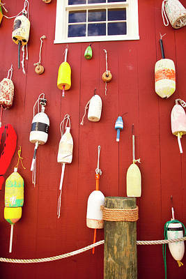 Lobster Pot Buoys Along A Red Wall Print by Brian Jannsen
