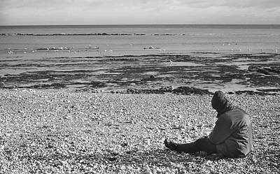 Black And White Photograph - Lone Man Sitting On Pebble Beach by Natalie Kinnear