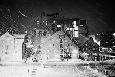 looking out atTromso bryggen quay harbour on a cold snowy winter night troms Norway europe Print by Joe Fox