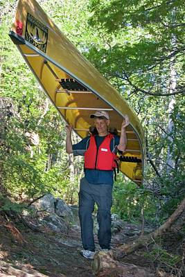Canadian Sports Photograph - Man Carrying A Canoe by Jim West