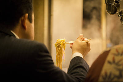 Man Eating Noodles In A Restaurant Print by Ruben Vicente